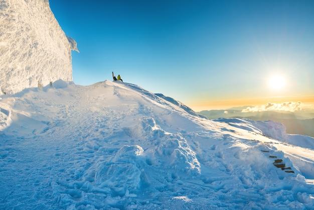 눈이 내리는 겨울 산 꼭대기에서 일몰을 바라보는 두 사람