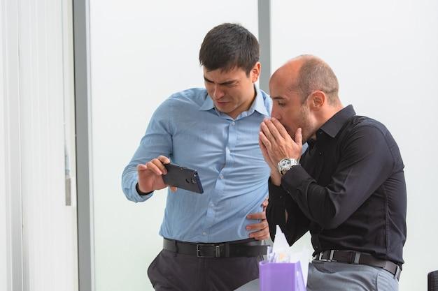 스마트폰을 보고 온라인 거래를 하는 두 사람