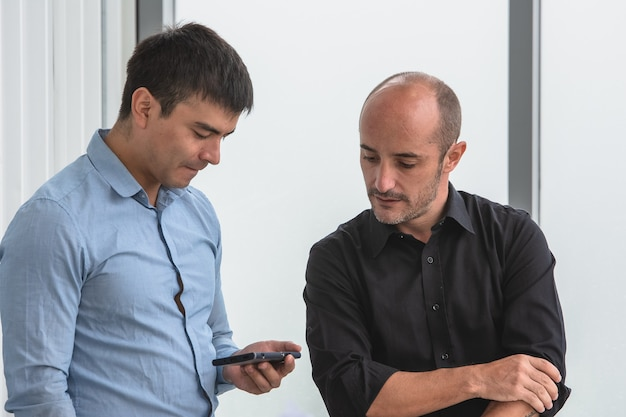 Two people looking on smartphone to trading online
