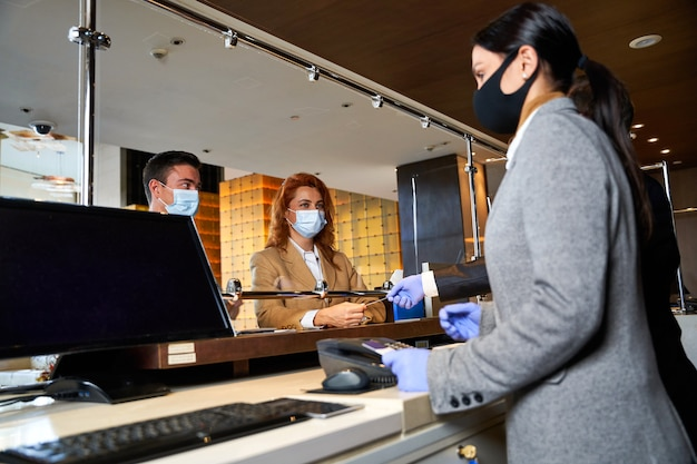 Two people in medical masks standing behind t glass shield in a hotel hall during the check-in