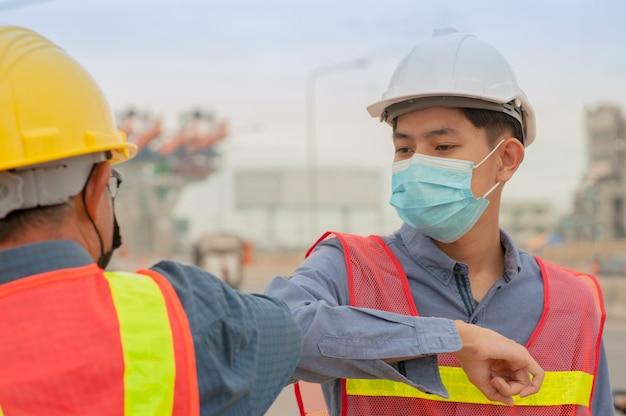 二人の新しい通常のこんにちは手を振らない社会的距離、エンジニアは手を振らないコロナウイルスを防ぐ、covid-19