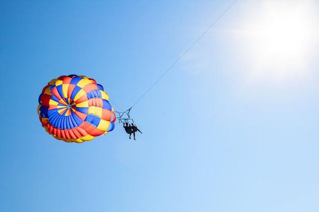 낙하산에 두 사람이 푸른 하늘에 바다 위로 날아
