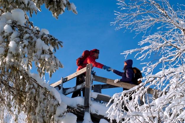冬の山の装備されたトレイルにいる2人
