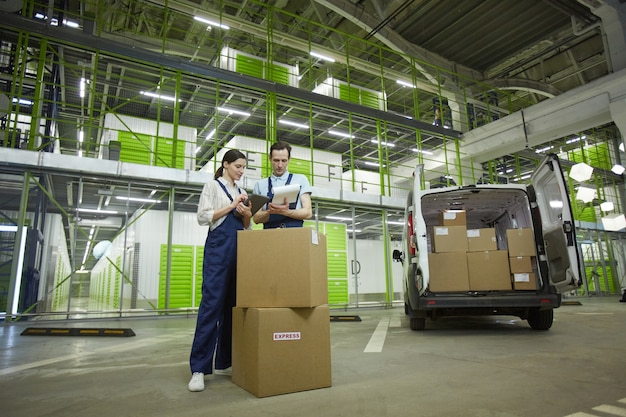 Два человека упаковывают посылки в коробки во время работы в службе доставки
