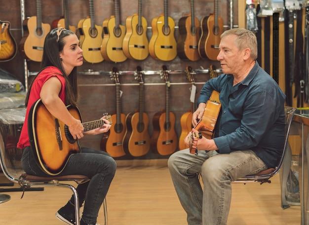 Два человека играют на гитаре в магазине классической гитары