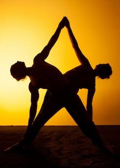 夕日の光の中でヨガを練習する二人