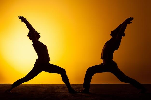 Два человека практикующих йогу в лучах заката