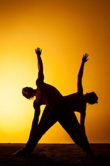 夕日の光の中でヨガを練習する2人