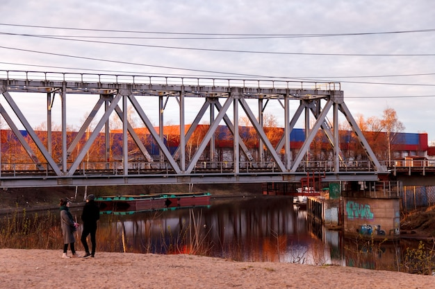 Two people in a railway bridge in an industrial area of the city