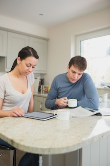 Two people reading from tablet pc and magazine