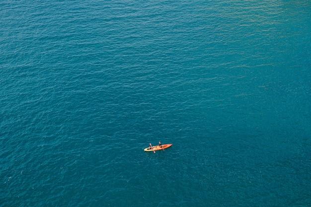 2 人が 1 つの黄赤色のカヤックでオールを漕ぎ、海のコンセプト バナー トラベルのテクスチャに対して