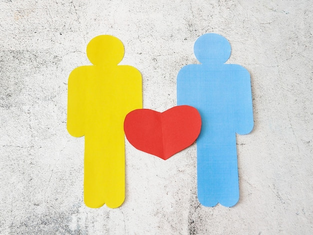 Два человека подписывают символ сердца бумаги