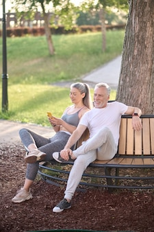Два человека сидят на скамейке в парке и отдыхают после тренировки