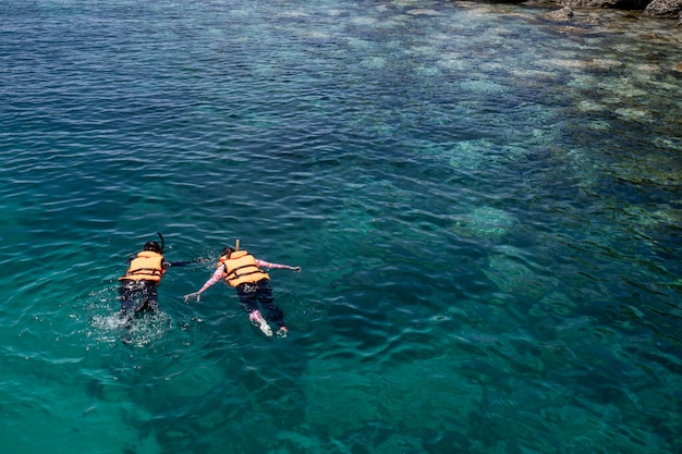 Два человека занимаются сноркелингом в спасательных жилетах над коралловым рифом с чистой голубой водой океана в тропическом чистом море