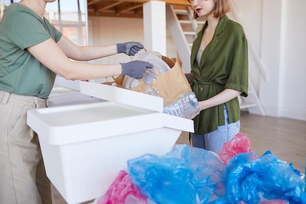 自宅でプラスチック製品を分別し、リサイクルのために廃棄物を準備する2人