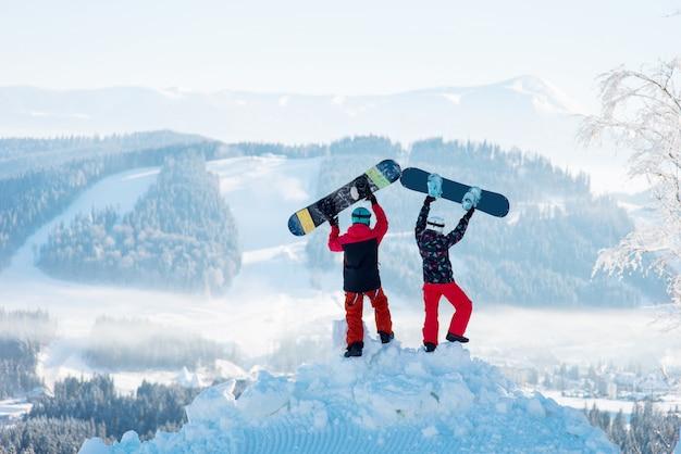 두 사람이 눈 더미에 등을 대고 서서 겨울 스키장에서 눈 덮인 산과 숲의 하얀 안개에 대항하여 스노우 보드를 들어 올립니다.