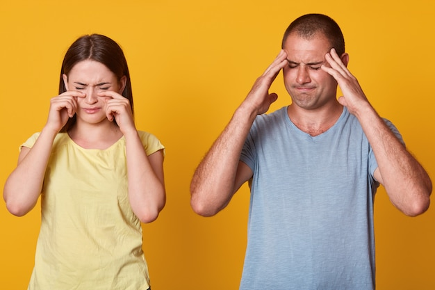 Two people standing in front of camera, female crying and looking disappointed, male keeps hands on temples and does not like her girlfriend behavior. love, relationship, people emotions concept.