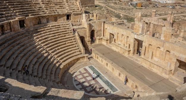 Двое людей днем стоят в старинном амфитеатре