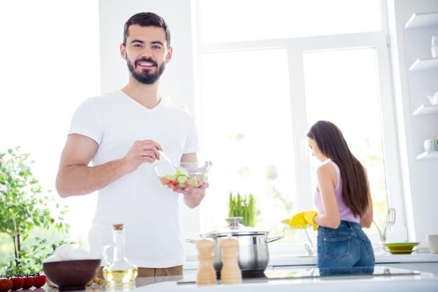 Два человека остаются дома на кухне, готовят вместе