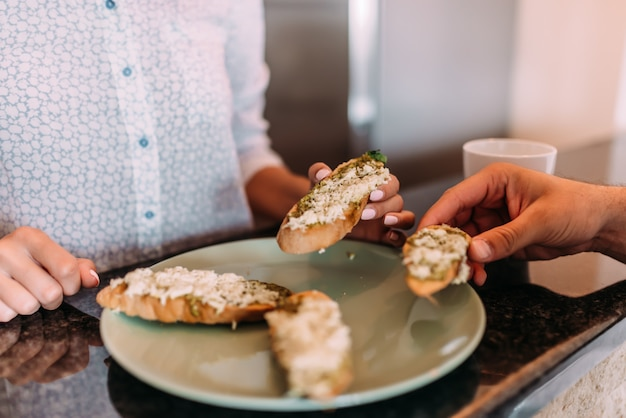 Two people taking homemade sandwich from a plate. close-up.