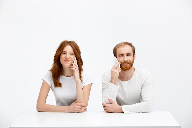 Два человека разговаривают по мобильному телефону рядом друг с другом