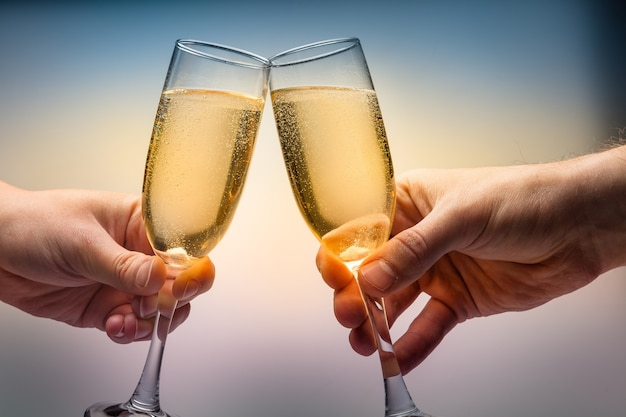 Two people toasting with wine glasses on background
