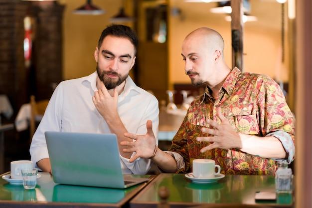 Два человека используют ноутбук на встрече в кафе.