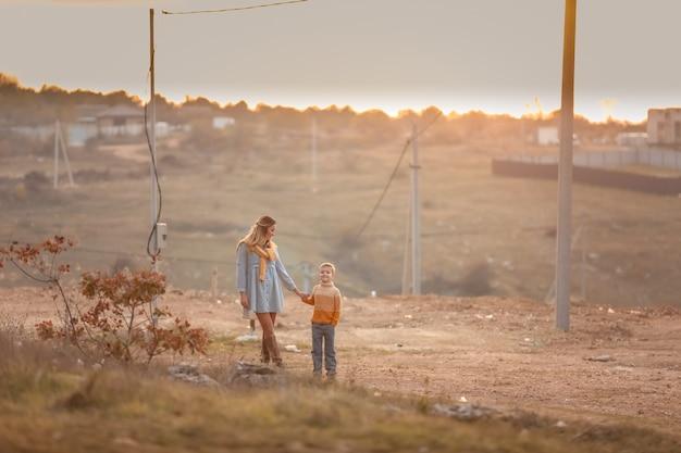 Два человека идут по деревенской дорожке, держась за руки