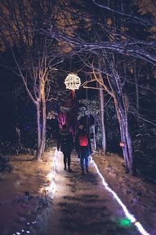 夜、木々の間の小道を歩く二人