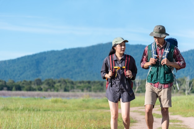 Two people walking on path in meadow. male and female traveler looking at attraction view