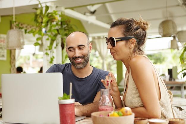 昼食時にラップトップコンピューターのwi-fiを使用して、オンラインでビデオを見たり、インターネットで写真を見たりする2人の人々。幸せなひげを生やした男とノートブックカフェでリラックスした色合いのスタイリッシュな女性。