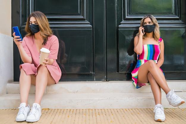 フェイスマスクを着用し、屋外で携帯電話を使用しながら距離を保つ2人。新しい通常のライフスタイルのコンセプト。