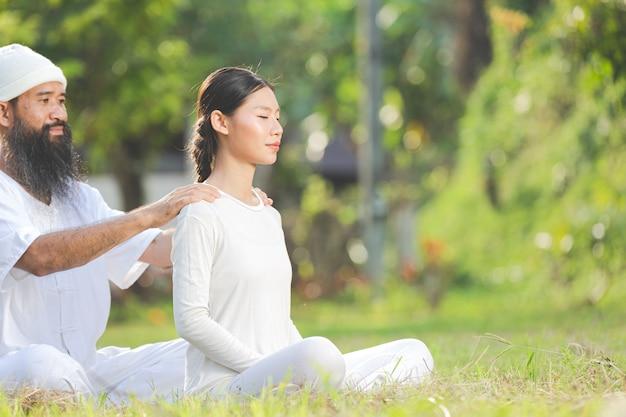 Due persone in abito bianco facendo massaggi con emozione rilassante