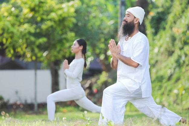 Due persone in abito bianco che fanno yoga in natura
