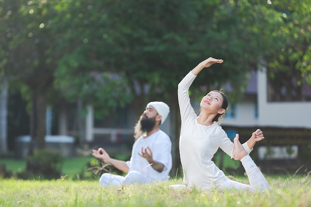 Two people in white outfit doing yoga in nature