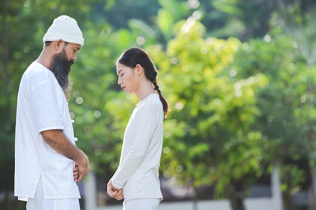 Two people in white outfit meditating in nature