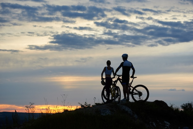 Two people with mountain bikes stand on top of cliff at sunset