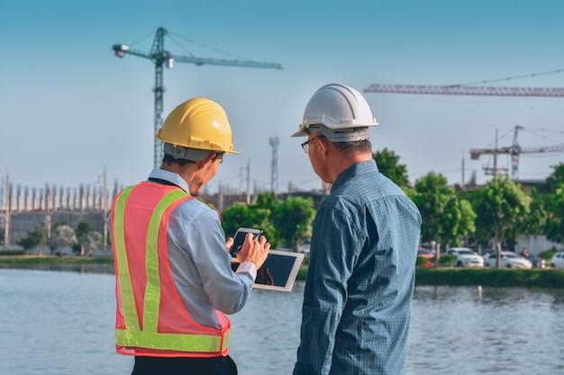 두 사람이 노동자 엔지니어가 부동산 건설 현장에서 태블릿으로 토론을 이야기합니다.