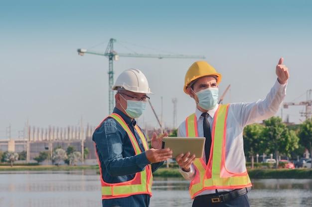 Два человека работают на стройке, а потом говорят о строительном проекте