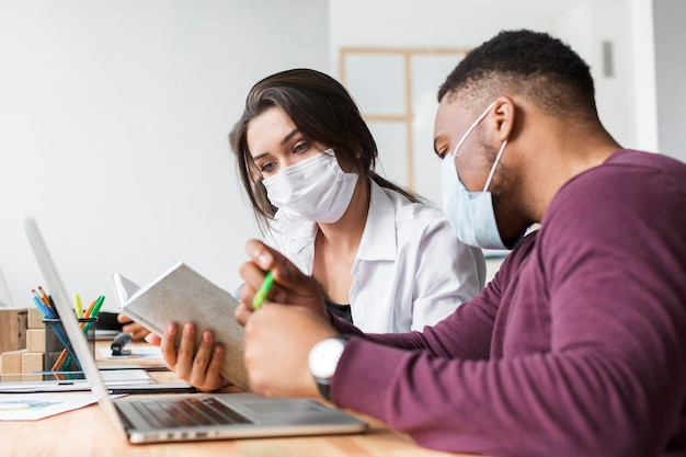 Two people working together in the office during pandemic with masks on