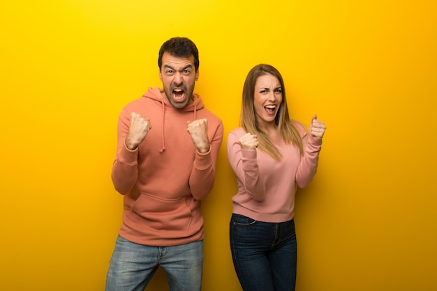 Two people on yellow background frustrated by a bad situation