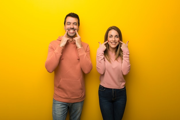 Two people on yellow background smiling with a happy