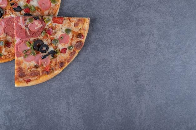 Два кусочка пиццы пепперони на сером фоне.