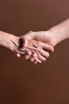 Two person from different generation shaking hands in an agreement