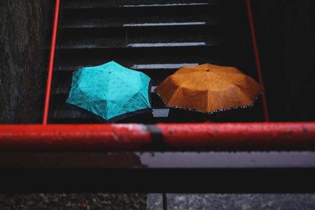 청록색과 갈색 우산을 들고 두 사람