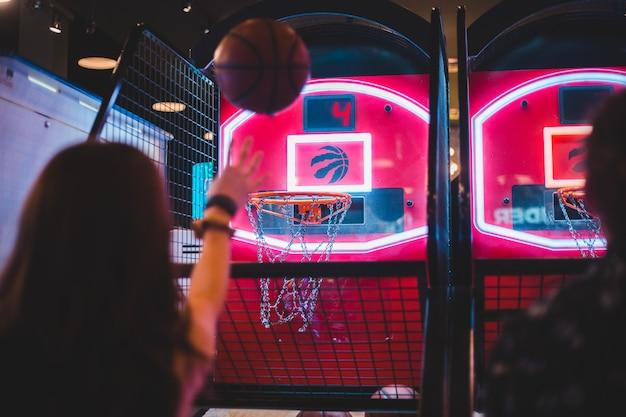 バスケットボールアーケードゲームをプレイする2人