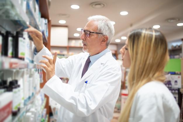 Два фармацевта проверяют свои запасы в аптеке