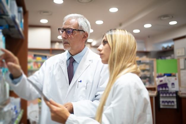 Two pharmacists checking their inventory in their pharmacy