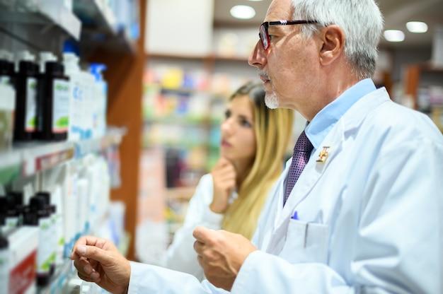 棚で商品を探している男性と女性の2人の薬剤師