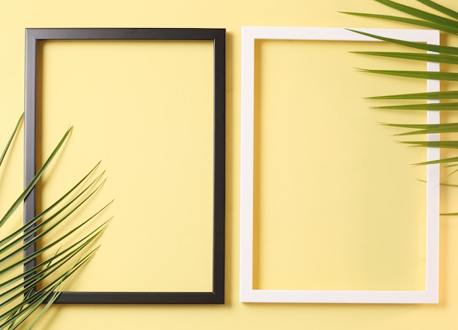 Two photo frame and palm leaves on pastel yellow background